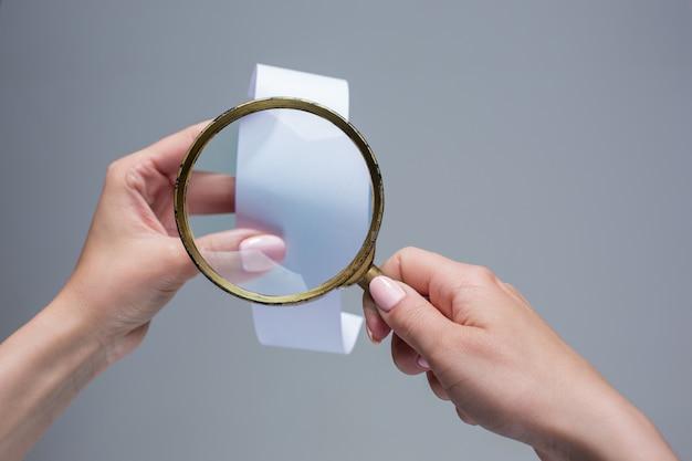 As mãos femininas com papel de transação vazio ou cheque e lupa