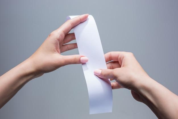 As mãos femininas com papel de transação vazio ou cheque
