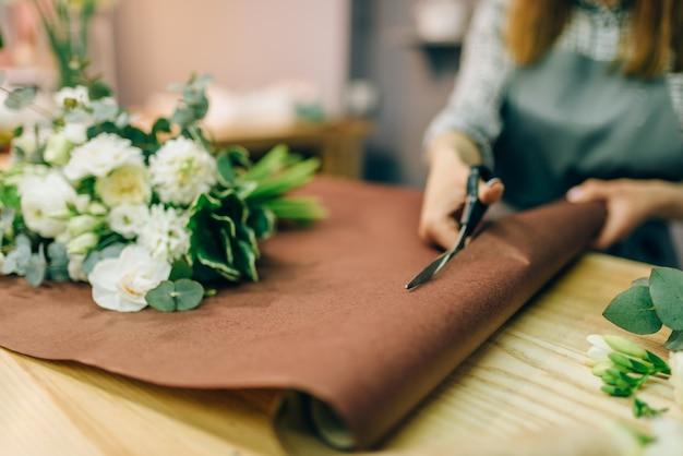 As mãos femininas da florista cortam a decoração com uma tesoura