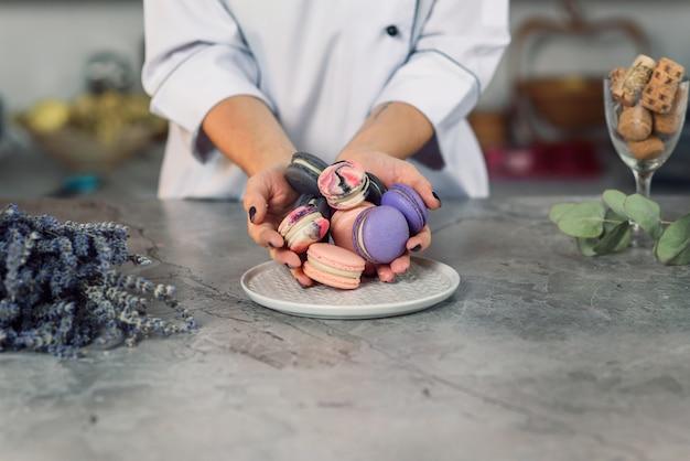 As mãos femininas de baker despejam macarons coloridos em um prato branco sobre uma mesa de mármore.