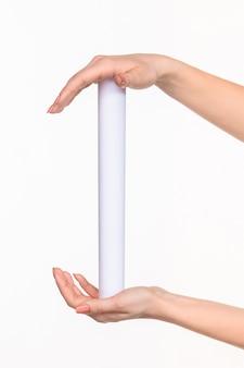 As mãos femininas do cilindro no espaço em branco