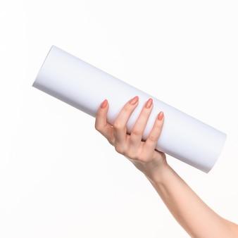 As mãos femininas do cilindro no fundo branco