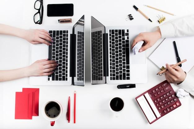 As mãos femininas e masculinas no local de trabalho