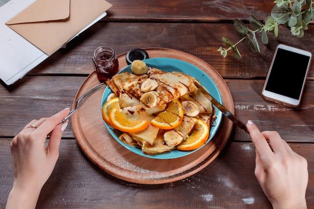 As mãos femininas e panquecas com suco. café da manhã saudável