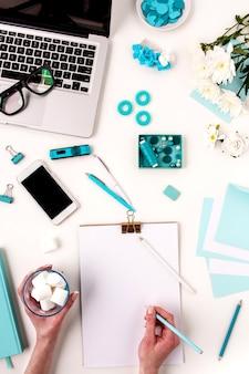 As mãos femininas escrevendo contra objetos de mulher moda azul em branco. conceito de maquete feminina