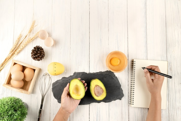 As mãos femininas fazem anotações no livro de dieta, vista superior, conceito, cópia espaço, mão segurando o abacate
