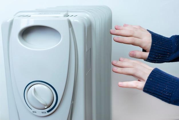 As mãos femininas procuram o radiador para se aquecer