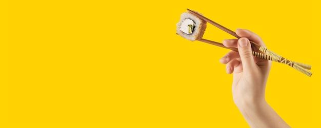 As mãos femininas seguram rolos de sushi com palitos. fundo amarelo. conceito criativo