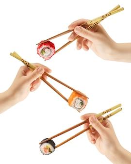 As mãos femininas seguram rolos de sushi com palitos. superfície branca. conceito criativo. traçado de recorte.