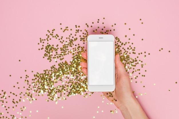 As mãos femininas seguram um telefone celular com confetes de estrelas douradas em papel rosa