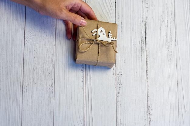 As mãos femininas seguram uma caixa de presente decorada de natal ou ano novo. fundo de madeira claro.
