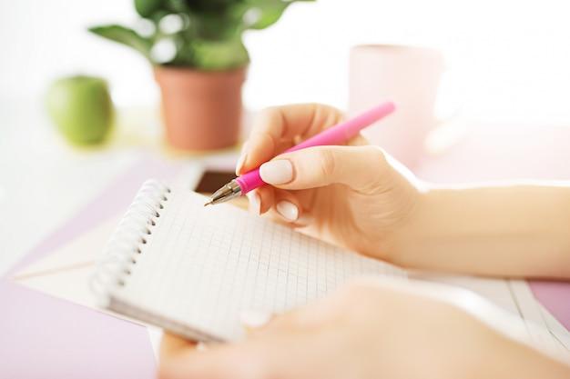 As mãos femininas segurando a caneta