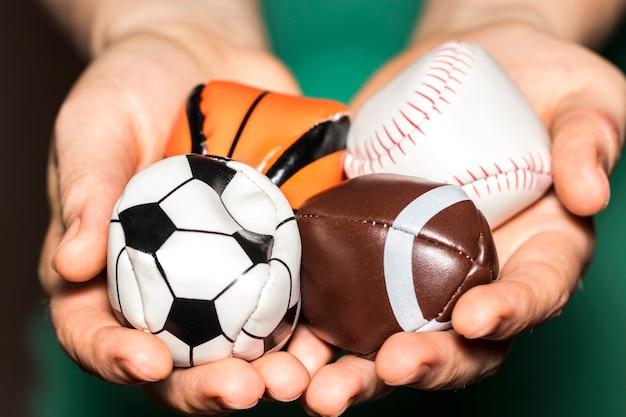 As mãos femininas segurando a coleção de bola de esporte com futebol, rugby, beisebol e basquete.