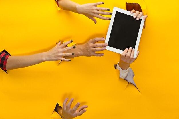 As mãos femininas segurando um tablet através de um papel amarelo rasgado, o conceito de venda e compras