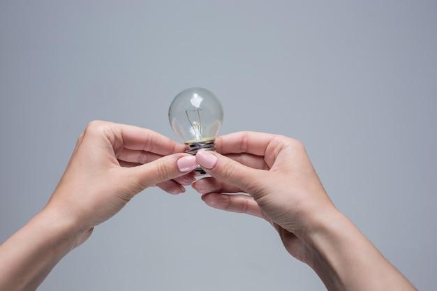 As mãos femininas segurando uma lâmpada incandescente em cinza