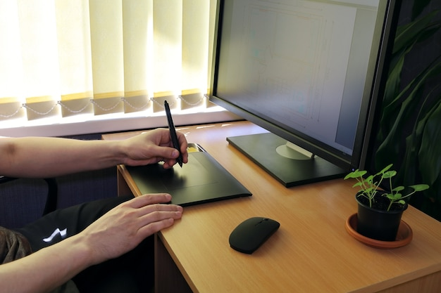 As mãos funcionam na mesa gráfica na frente do monitor