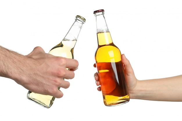 As mãos guardam garrafas da cidra, isoladas no branco. felicidades
