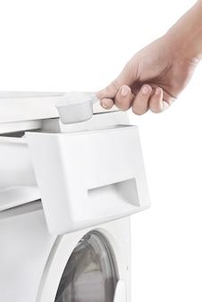 As mãos humanas colocam o detergente na máquina de lavar roupa
