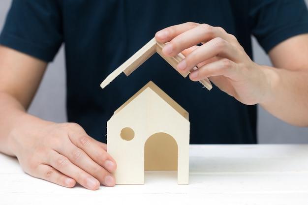 As mãos humanas tentam construir a casa de madeira do brinquedo, modelo home conceito da construção.