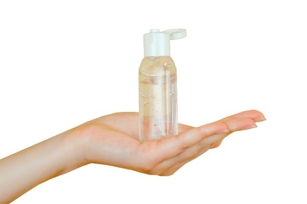 As mãos humanas usam um gel, desinfetante, anti-séptico em uma bolha, frasco em um fundo preto isolado