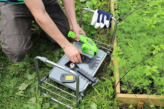 As mãos juntam e desmontam as ferramentas de jardim em uma mesa dobrável virada para baixo