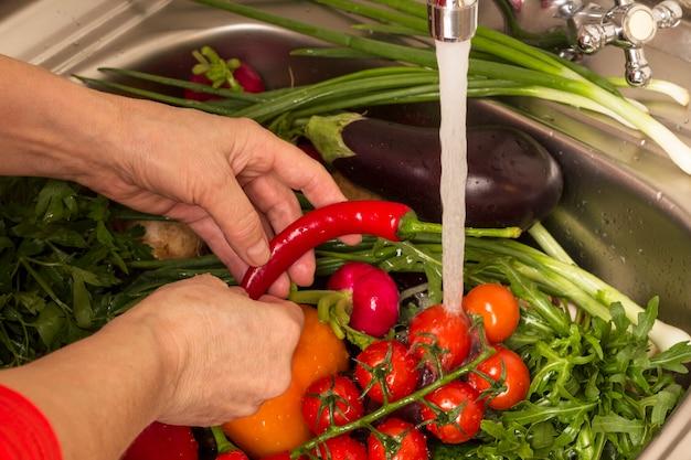 As mãos lavam legumes na pia.