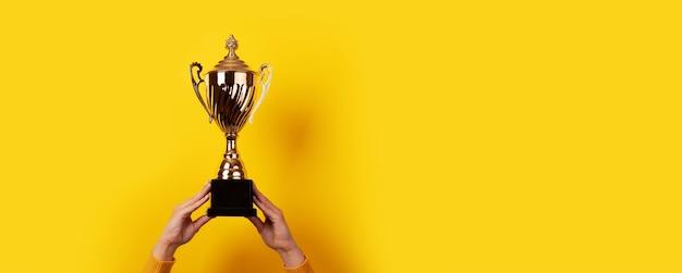 As mãos levantadas de uma mulher segurando um troféu sobre fundo amarelo