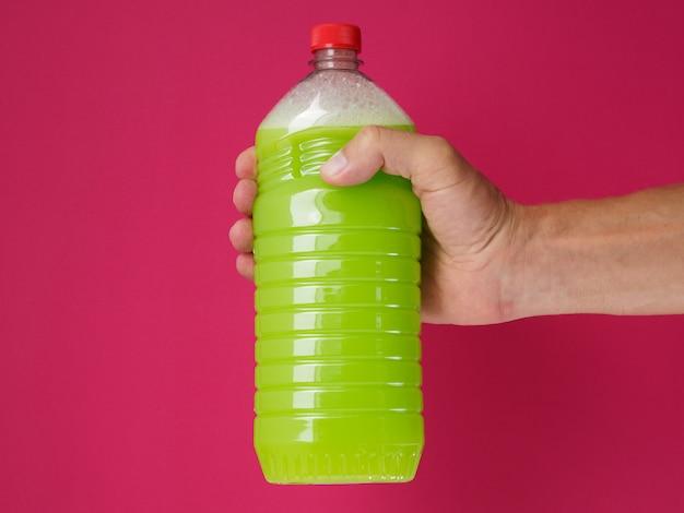 As mãos masculinas abrem uma garrafa de limpador de chão líquido verde sobre fundo rosa.