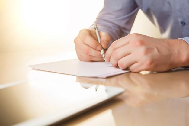 As mãos masculinas com uma caneta e o copo