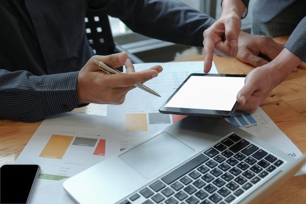 As mãos masculinas do businessteam trabalham na calculadora e na tabuleta no escritório.