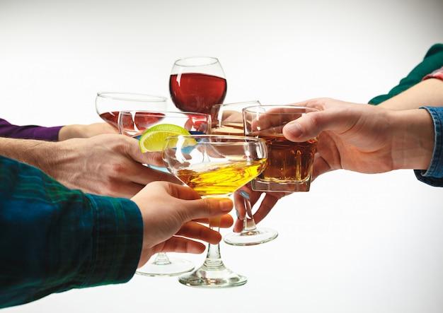 As mãos masculinas e femininas com cocktails exóticos