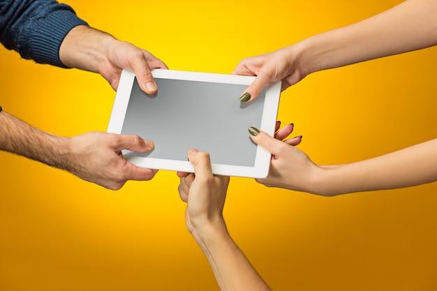 As mãos masculinas e femininas usando tablet pc com tela preta, isoladas