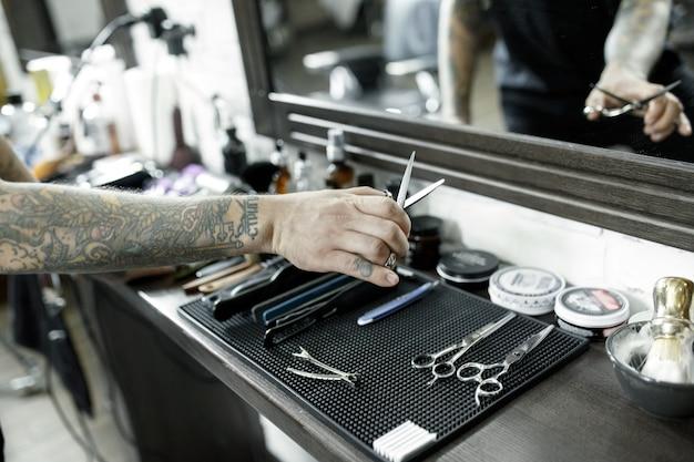 As mãos masculinas e ferramentas para cortar a barba na barbearia. ferramentas vintage de barbearia. a mão do mestre tem tatuagem com a palavra barbear