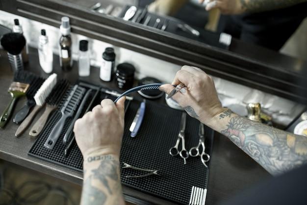As mãos masculinas e ferramentas para cortar a barba na barbearia.