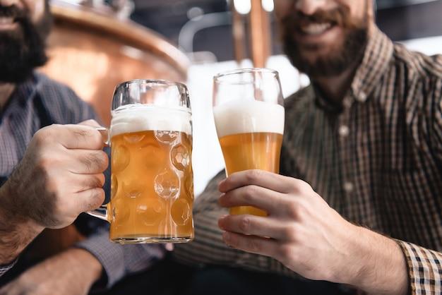 As mãos masculinas guardam a cerveja ale fresca no vidro e na caneca.