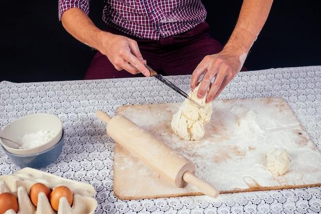 As mãos masculinas na farinha e no pão rústico orgânico se preparam para fazer as massas bio italianas, as pizzas, as tortas