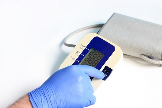 As mãos masculinas usam a tecla de começo da imprensa da luva no medidor da pressão sanguínea no fundo branco.