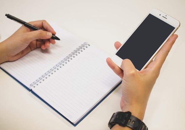 As mãos na caneta e usando o smartphone ao mesmo tempo.