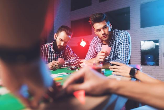 As mãos na mesa mostram cartas na sala de jogos.