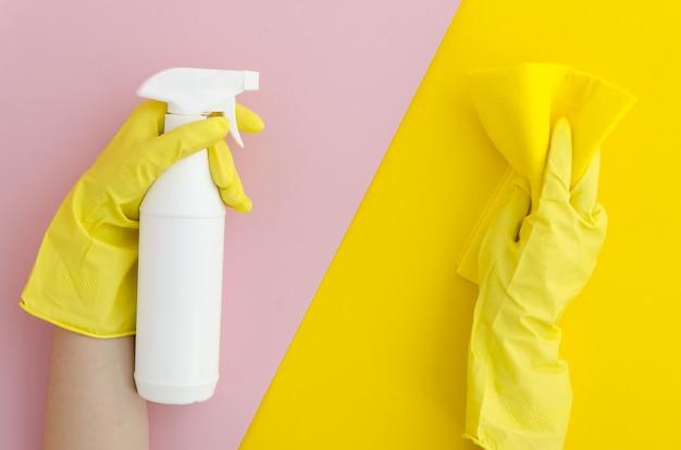 As mãos nas luvas de borracha amarelas guardam o pulverizador, conceito de limpar o serviço.
