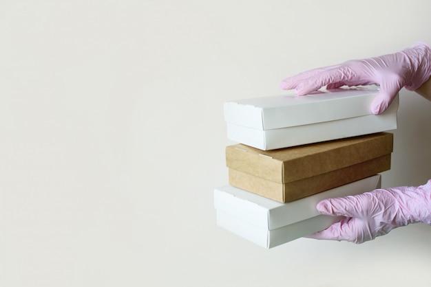 As mãos nas luvas seguram caixas de comida ecológica para entrega sobre um fundo claro. lugar para texto