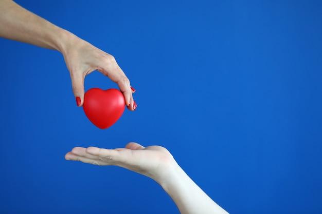 As mãos passam o coração vermelho conceito de doença cardíaca