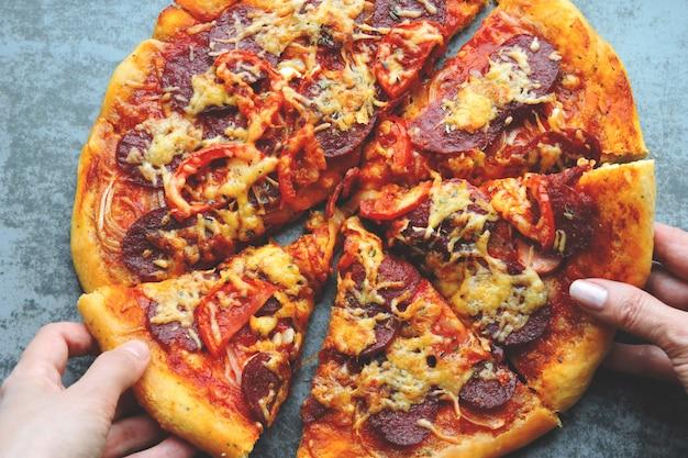 As mãos pegam uma fatia de pizza.