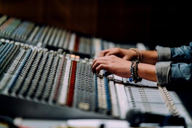 As mãos profissionais nas proximidades da mesa de som estão misturando sons pelo painel de controle do mixer de áudio.