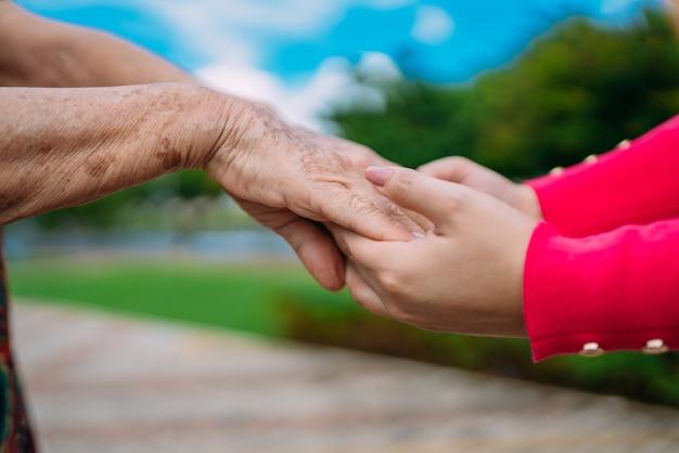 As mãos que ajudam no atendimento domiciliar de idosos em um parque ao ar livre.