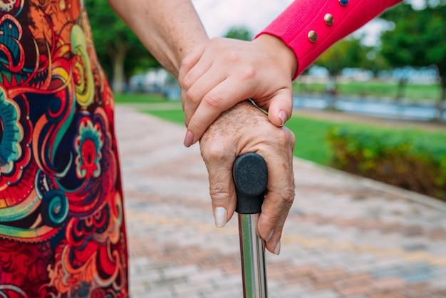 As mãos que ajudam para cuidados domiciliares de mulher idosa bengala em um parque ao ar livre.
