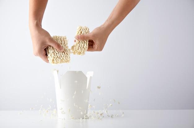 As mãos quebram o pacote prensado de macarrão seco acima da caixa para viagem em branco aberta antes da preparação. conjunto promocional de varejo comercial