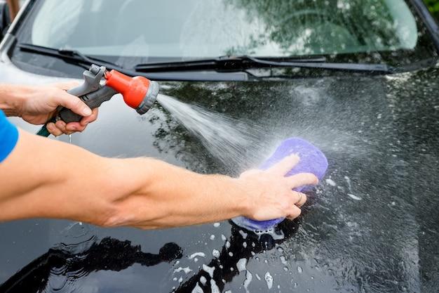 As mãos seguram a esponja para lavar o carro.