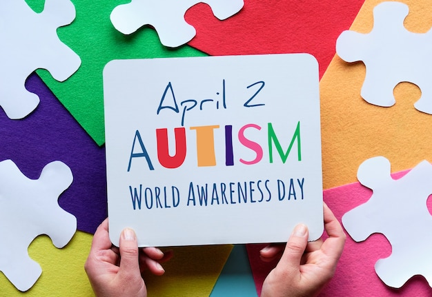As mãos seguram a prancha com o texto 2 de abril, dia da conscientização mundial do autismo