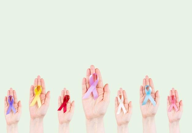As mãos seguram fitas multicoloridas, símbolo da luta contra o câncer. dia mundial do câncer